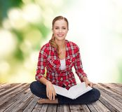 Smiling young woman sitting on floor with book Stock Image