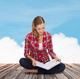 Smiling young woman sitting on floor with book Royalty Free Stock Photography