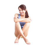 Smiling young woman sitting on floor Royalty Free Stock Photos
