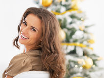Smiling young woman sitting in front of christmas tree Stock Image