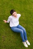 Smiling young woman sitting in the grass Royalty Free Stock Photography