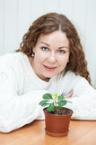 Smiling young woman sitting with green plant Stock Photo