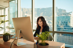 Smiling young woman sitting at her desk royalty free stock images