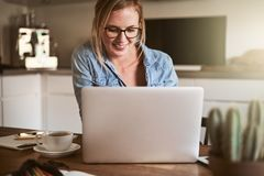 Smiling young woman working on her business at home. Smiling young woman sitting at her kitchen table at home working on her small business with a laptop royalty free stock image