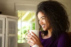 Smiling young woman sitting at home enjoying cup of coffee Royalty Free Stock Images