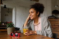 Smiling young woman sitting at home with glass of orange juice Royalty Free Stock Image