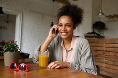 Smiling young woman sitting at home talking on mobile phone Royalty Free Stock Images