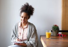 Smiling young woman sitting at home writing in note pad. Portrait of a smiling young woman sitting at home writing in note pad Royalty Free Stock Images
