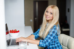 Smiling young woman sitting with a laptop Stock Image