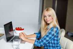 Smiling young woman sitting with a laptop Stock Photo