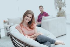 Smiling young woman sitting in a large comfortable chair. Smiling young women sitting in a large comfortable chair in the living room blurry background Stock Image