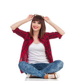 Smiling Young Woman Sitting With Legs Crossed Royalty Free Stock Photos