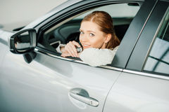 Smiling young woman sitting in new car and holding key Royalty Free Stock Image