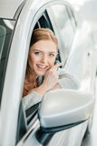 Smiling young woman sitting in new car and holding key Royalty Free Stock Photography