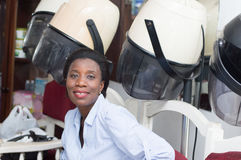 Smiling young woman sitting next to hair helmets. This young woman is sitting next helmets waiting her turn for her hairstyle Stock Photo