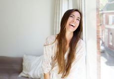 Smiling young woman sitting next to window Stock Photography