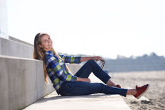 Smiling young woman sitting outdoors Stock Photo