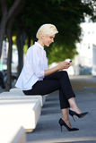 Smiling young woman sitting outside reading text message Royalty Free Stock Photos