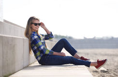 Smiling young woman sitting outside with sunglasses Royalty Free Stock Photo