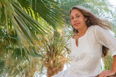 Smiling young woman sitting on palm tree. Concept happy rest, li royalty free stock photography