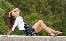 Smiling young woman sitting in a park Stock Images