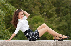 Smiling young woman sitting in a park Stock Photography