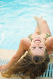 Smiling young woman sitting at poolside Stock Photography
