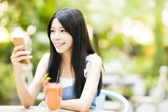 Young woman sitting in restaurant watching smart phone Royalty Free Stock Photography
