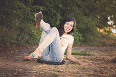 Smiling young woman sitting on road in park Stock Images