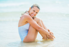 Smiling young woman sitting on sea shore Royalty Free Stock Image