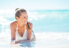 Smiling young woman sitting at seaside Royalty Free Stock Images