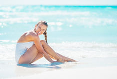 Smiling young woman sitting at seaside Royalty Free Stock Photography