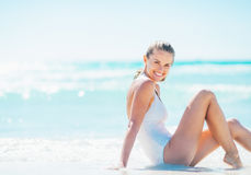 Smiling young woman sitting at seaside Stock Photography