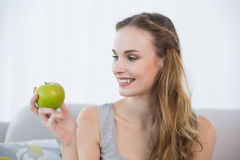 Smiling young woman sitting on sofa holding green apple Stock Image
