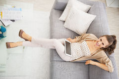 Smiling young woman sitting on sofa with tablet pc Royalty Free Stock Photo