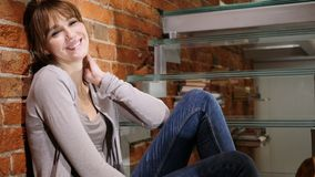 Smiling Young Woman Sitting on Stairs, Looking in Camera stock photography