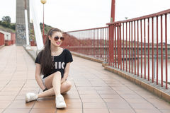 Smiling young woman sitting in the street. Royalty Free Stock Photo