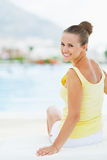 Smiling young woman sitting on sunbed Stock Photography