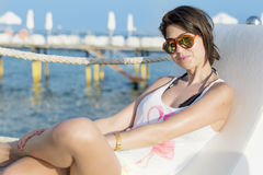 Smiling young woman sitting on a sunbed on a  sea background Royalty Free Stock Images