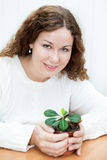 Smiling young woman sitting at the table and holding green plant Stock Images