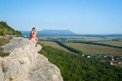 Smiling young woman sitting on the top of mountain Stock Photo