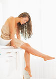 Smiling young woman sitting with wet hair in bathroom Stock Photography