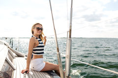 Smiling young woman sitting on yacht deck Royalty Free Stock Images