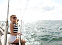 Smiling young woman sitting on yacht deck Royalty Free Stock Photos
