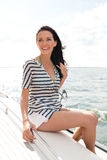 Smiling young woman sitting on yacht deck Royalty Free Stock Photography