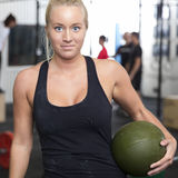 Smiling young woman with slam ball at gym center Royalty Free Stock Photography
