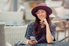 Smiling young woman with smart phone in cafe shop Royalty Free Stock Photos