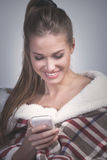 Smiling young woman with smartphone at home Stock Images