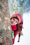 Smiling young woman in  snow park behind tree Stock Photo