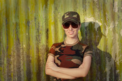 Smiling Young Woman Soldier in Camouflage Outfit. Portrait of a happy beautiful female army soldier stock photo